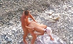 On a rocky beach a couple is fucking