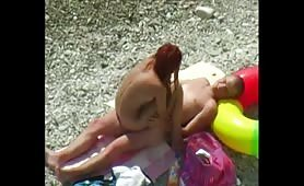 Redhead babe riding cock on rocky beach